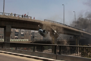 The police vehicle hits the bridge wall and fells off